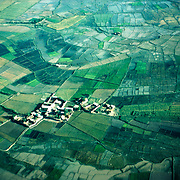 3 June 1976<br /> Village outside Kunduz highlighted by brilliant sun. Nuclear pattern surrounded by fields.