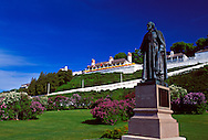 STATUE OF FATHER JACQUES MARQUETTE STANDS AMON BLOOMING LILACS ON THE LAWN BELOW FORT MACKINAC ON MACKINAC ISLAND, MICHIGAN.