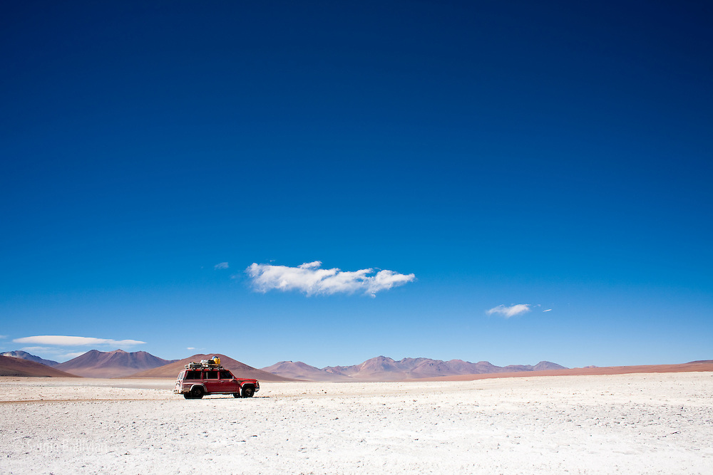 A 4x4 vehicle is seen on the desolate plains next to Laguna Verde at 14,500' above sea level, below the 20,000' Llicancabur Volcano deep in the Sud Lipez region of southwestern Bolivia.