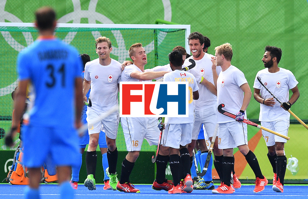 Canada's Scott Tupper (hidden) celebrates scoring with his teammates during the mens's field hockey India vs Canada match of the Rio 2016 Olympics Games at the Olympic Hockey Centre in Rio de Janeiro on August, 12 2016. / AFP / Carl DE SOUZA        (Photo credit should read CARL DE SOUZA/AFP/Getty Images)