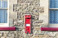Victorian red post box (with the letters V R) embedded into a house wall in Richmond, Yorkshire, UK