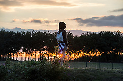 © London News Pictures. Calais, France. An immigrant watches over the train tracks at sunset at the perimeter to the Eurotunnel complex.  Migrants attempting to reach the UK via the Eurotunnel at Calais in France. The situation has reached crisis point, which French police over run by attempts to cross the border. Photo credit: Ben Cawthra /LNP
