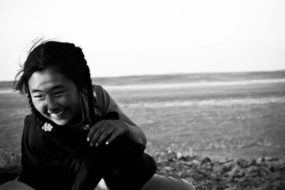 A young girl smiles near sunset in rural Mongolia.