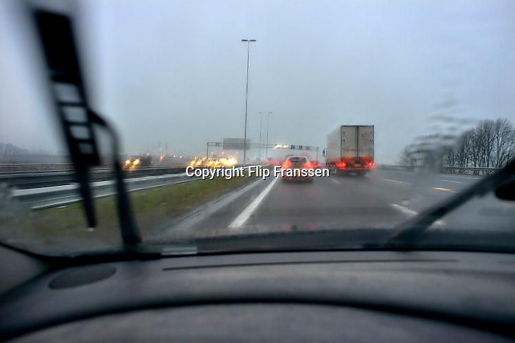 Nederland, A15, 21-11-2017Regen tijdens het rijden op de snelweg, autorijden is erg vermoeiend en kan tot extra gevaarlijke situaties leiden. Ruitenwissers zijn niet altijd in goede conditie.Foto: Flip Franssen