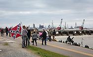 """an. 10, 2015, Norco. Louisiana, A man holding a Conferadte flag waering a gun on his side, watches along with a crowd of spectors as cranes on the weir forming a wall between the Mississippi River and the Bonnet Carre Spillway start removing creosoted timber, """"needles"""" from the first of 350 bays to reduce the Mississippi's water-flow as it approaches New Orleans, directing it into Lake Pontchartrain."""