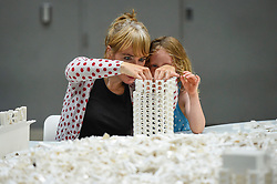 "© Licensed to London News Pictures. 26/07/2019. LONDON, UK. Willow Beal, aged 5, and her mother work with Lego at the preview of ""The cubic structural evolution project"", 2004, by Olafur Eliasson at Tate Modern.  Exhibited for the first time in the UK, the artwork comprises one tonne of white Lego bricks inspiring visitors to create their own architectural vision for a future city and is on display until 18 August 2019.  The work coincides with the artist's new retrospective exhibition ""In real life"" at Tate Modern on display to 5 January 2020.  Photo credit: Stephen Chung/LNP"