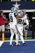 Dallas Cowboys wide receiver Amari Cooper (19) congratulates Dallas Cowboys running back Ezekiel Elliott (21) with a pat on the helmet after Elliott catches a 16 yard touchdown pass good for a 10-0 first quarter Cowboys lead during the NFL week 13 regular season football game against the New Orleans Saints on Thursday, Nov. 29, 2018 in Arlington, Tex. The Cowboys won the game 13-10. (©Paul Anthony Spinelli)