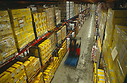 From high above the stacked crates and pallets of duty free merchandise at the British Airports Authority (BAA) secure facility near London Heathrow airport, a blurred forklift truck drives down a corridor moving fast away from two people in the background. In the foreground yellow boxes contain Gordon's Gin and Benson & Hedges cigarettes destined for the airports and aircraft leaving BAA terminals. We see the diagonal lane in this warehouse the size of a hangar, so vast is its scale. The workers in the distance appear dwarfed against the tall shelves of merchandise that they need to organise and keep a tally of. It is a picture of ultimate organisation and the efficient transporting of goods in and out of this logistics hub.