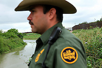 Leonel Guerrero, a Senior Patrol Agent with the U.S. Border Patrol, looks out on the US-Mexico border, in front of the agent is the Rio Grande, which creates the border between the two countries, behind him lies a stretch of the newly constructed border fence, in Brownsville, TX on April 21, 2010. (Photo/Scott Dalton)