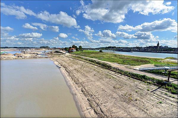 Nederland, Nijmegen, 25-6-2015De nevengeul aan de overkant van de Waal bij Lent nadert zijn voltooiing. Laatste werkzaamheden. Grootste onderdeel van de vele werken van Rijkswaterstaat om bij hoogwater een betere waterafvoer in de rivier te hebben. Het is een omvangrijk project waarbij onder meer de pijlers van het spoorviaduct een bredere basis kregen omdat die straks in de loop van het water staan. Ook de n325 die vanaf de Waalbrug naar Arnhem loopt is over 400 meter opnieuw aangelegd omdat het talud vervangen wordt door een nieuwe brug met drie gracieuze pijlers. Het dorp veurlent komt op een kunstmatig eiland te liggen met twee bruggen als ontsluiting. Een voetgangersbrug en een andere, de Promenadebrug, voor normaal verkeer. Inmiddels begint de nieuwe kade aan de noordkant van deze geul vorm te krijgen. Ruimte voor de rivier, water, waal. In de nieuwe dijk wordt een drempel gebouwd die stapsgewijs water doorlaat en bij hoogwater overloopt.The Netherlands, NijmegenMeasures taken by Nijmegen to give the river Waal, Rhine, more space to flow during highwater and to prevent the risk of flooding. Room for the river. Reducing the level, waterlevel. Large project to create a new paralel gully, an extra flow of water, so the river can drain more water during highwater. Due to climate change and expected rise, increase of the sealevel, the Dutch continue to protect their land from the water.Foto: Flip Franssen/HH