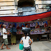May 18, 2013 - Yangon, Myanmar: Locals pass by a street stall selling religious portraits in central Yangon. CREDIT: Paulo Nunes dos Santos