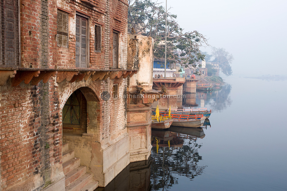 View of boats, ghats and houses on the Yamuna river, Mathura, India.