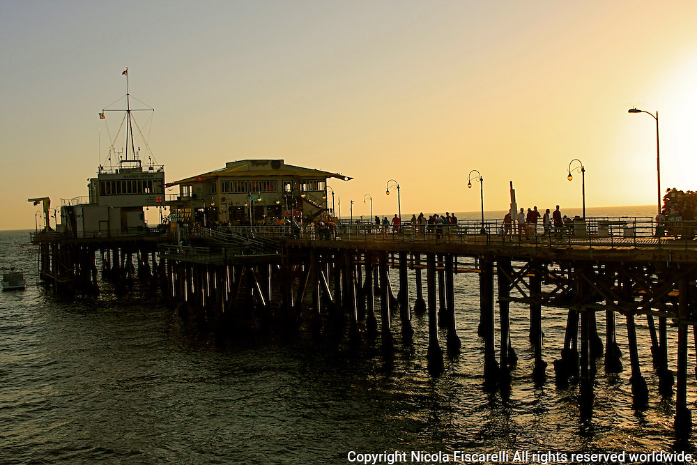 The late afternoon sun's rays are piercing thru the  pillars of the Santa Monica  California    Pier.