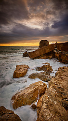 A romantic couple looking at the Pulpit Rock with a stormy sky sunset behind them and ocean waves breaking over the rocks in the foreground.<br /> <br /> Portland Bill in Dorset, England