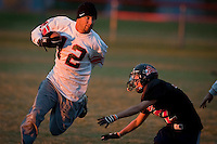 """JEROME A. POLLOS/Press..Jeff Johnson, a class of 2000 graduate from Post Falls High, blows past the reach of Marc Conradi, 14, who plays for the Post Falls eighth-grade Trojan football team during a """"new vs. old"""" pick-up game Tuesday at Post Falls High."""