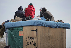© Licensed to London News Pictures. 02/03/2016. Calais, France. Migrants camp out on the roof of a temporary building at the migrant camp knows as 'The Jungle' in Calais, France, where part of the camp is currently being cleared by French authorities. Violence has broken out in parts of the eviction zone where inhabitants have resisted efforts to move them. Photo credit: Rob Pinney/LNP