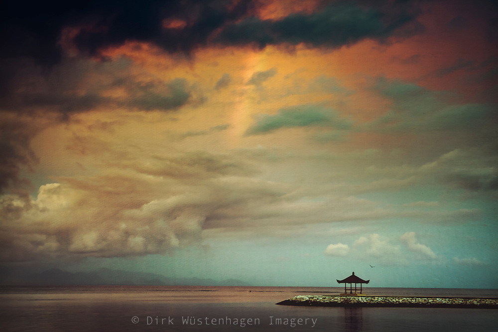 Jetty and pavillion at the near Sanur Beach, Bali, Indonesia. Evening light and rain showers create a rainbow....