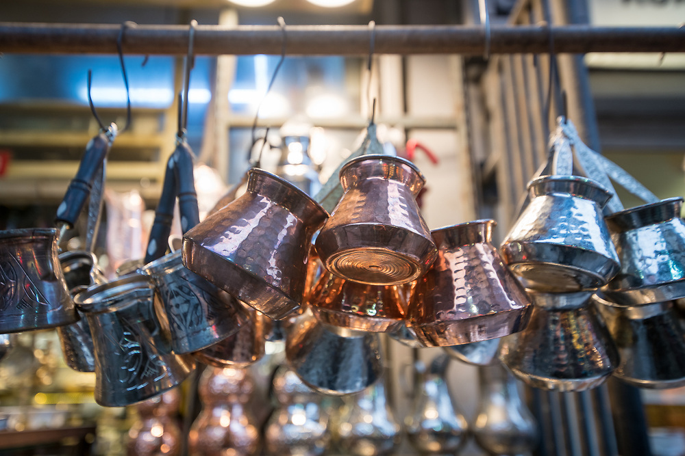 Silver and copper cezves hang on display for sale at Istanbul Spice bazaar in Turkey