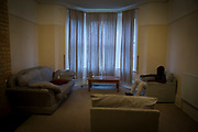 An unaccompanied minor refugee child sits alone in his front room where he has been recently housed. United Kingdom. Housing conditions are often a little bare and bleak for new arrivals.  (photo by Andrew Aitchison / In pictures via Getty Images)