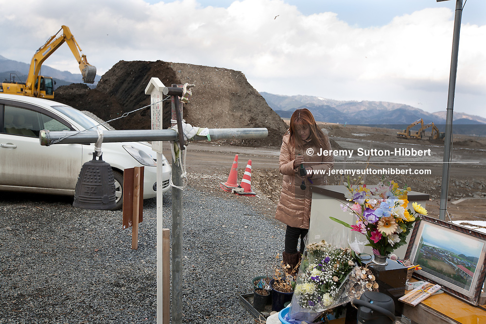 Miho Suzuki (no face mask, light brown coat) prays, along with her mother (face mask, dark brown coat), at a shrine to the memory of her daughter Hana, and the other 73 children and ten teachers who lost their life in the tsunami that followed the earthquake of March 11th 2011, at Okawa Elementary School in Okawa village, near Ishinomaki, Japan, on Friday 17th February 2012..Miho Suzuki lost her daughter Hana, whose body has not yet been recovered, and also her son Kento who has been found dead.