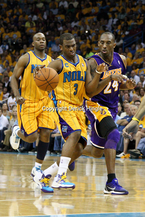 April 22, 2011; New Orleans, LA, USA; New Orleans Hornets point guard Chris Paul (3) drives past Los Angeles Lakers shooting guard Kobe Bryant (24) during the second quarter in game three of the first round of the 2011 NBA playoffs at the New Orleans Arena.    Mandatory Credit: Derick E. Hingle