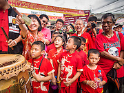 """19 FEBRUARY 2015 - BANGKOK, THAILAND: A woman and children watch a lion dance troupe during Chinese New Year festivities in Bangkok. 2015 is the Year of Goat in the Chinese zodiac. The Goat is the eighth sign in Chinese astrology and """"8"""" is considered to be a lucky number. It symbolizes wisdom, fortune and prosperity. Ethnic Chinese make up nearly 15% of the Thai population. Chinese New Year (also called Tet or Lunar New Year) is widely celebrated in Thailand, especially in urban areas that have large Chinese populations.    PHOTO BY JACK KURTZ"""