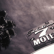 Toned, black&white shot of Fabulous 7 Motel signage in El Cajon, CA. Shot in the daytime with dramatic, dark sky and palm tree, looking upward