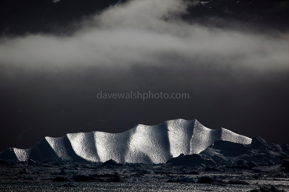 Sleeping Dragon, Kangerdlugssuaq Fjord, East Greenland. Limited edition C-Type Prints available - contact me for more details.<br /> <br /> <br />  This iceberg is calved from Kangerdlussuaq glacier, the largest glacier on the east coast of Greenland's ice sheet and probably the world's fastest moving glacier. Kangerdlugssuaq tripled its speed between 2004 and 2005, and is now rapidly moving mass out of the middle of Greenland's ice sheet, in the form of icebergs. This has urgent implications for both the mass balance of the Greenland ice sheet, and for the rate of sea level rise globally.<br /> Taken from the deck of the Greenpeace ship Arctic Sunrise, during a 2009 expedition to investigate the effects of climate change in the Arctic.