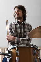Young man sits at drumset with arms crossed holding drumsticks