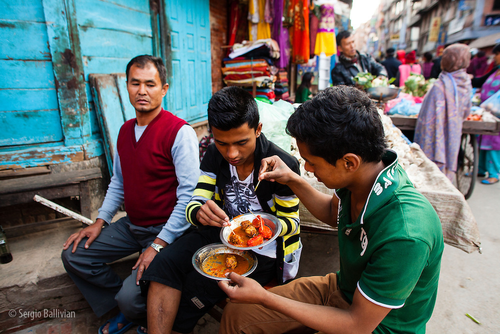 People eat typical Nepali food in the open air markets in Patan, east of Kathmandu, Nepal.