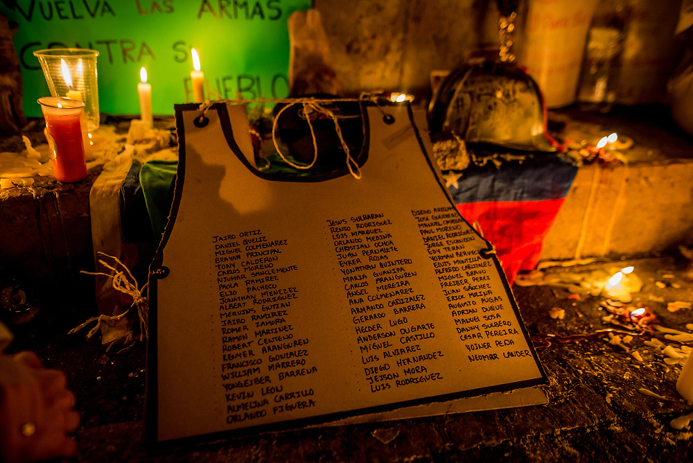 "CARACAS, VENEZUELA - JUNE 8, 2017: A cardboard cut-out with the names of all the people killed during recent anti-government protests in Venezuela bearing a likeness to the protective vest made of carpet that protester Neomar Lander was wearing when he was killed by security forces. Members of ""The Resistance"" lit candles and construct a makeshift memorial around the blood-stained spot on the road where Neomar Lander, 17, was killed. Johan Caldera, a close friend of Mr. Lander said he is even more determined to protest since his friend was killed.  ""Now, I have no fear - because I already lost the fear I had, and the respect for the military. The little respect I had, is gone. Now, the real soldiers of Venezuela wear rags on their faces, they wear a glove and they they don't use grenades - they use stones, they use their will, and they use their balls to go out into the street."" He said he had discussed with Neomar the possibility of being killed during the protests, ""and he [Neomar] told me: brother, if I die - if I lose my life during a protest, I don't want everyone to stop marching, I want them to march double and keep going to the street for a week, every single day, day and night without fear.""  PHOTO: Meridith Kohut"