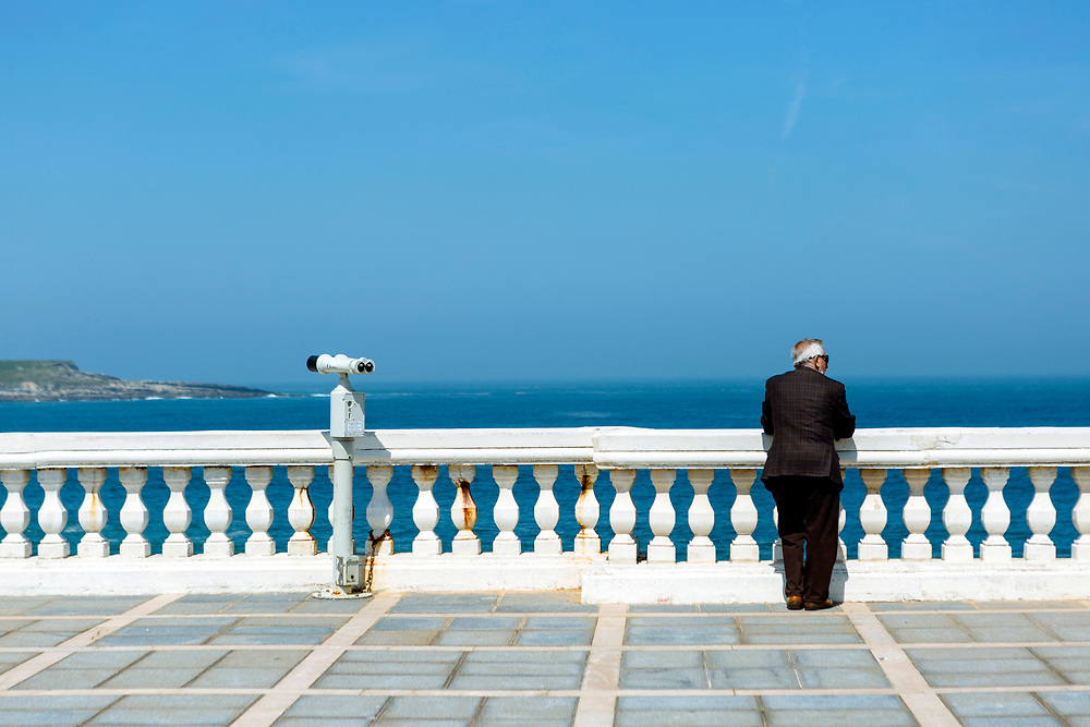 SANTANDER, SPAIN - April 18 2018 -  Person looks out to sea view in opposite direction to pay per view binoculours, Santander, Northern Spain, Europe.