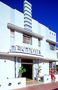 A handsome, shirtless man leans against the wall of the stylish Century Hotel on Ocean Drive in Miami Beach's historic South Beach. The building was designed by Henry Hohauser in 1939, and remains an outstanding example of the neighborhood's signature Tropical Deco style.