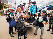 09 JULY 2014 - ARANYAPRATHET, SA KAEO, THAILAND:  Cambodian migrants get out of a Thai police pickup truck at the immigration station in Aranyaprathet. The Thai government has opened a One Stop Service Center in Aranyaprathet on the Thai-Cambodian border. More than 200,000 Cambodian migrant workers, most undocumented, fled Thailand in early June fearing a crackdown by Thai authorities after a coup unseated the elected government. Employers have been unable to fill the vacancies created by the Cambodian exodus and the Thai government has allowed them to return. The Cambodian workers have to have a job and their employers have to vouch for them. The Thai government is issuing temporary ID cards to allow them to travel openly to their jobs. About 800 Cambodian workers came back to Thailand through the Aranyaprathet border crossing Wednesday. The Thai government has opening similar service centers at three other crossing points on the Thai-Cambodian border.   PHOTO BY JACK KURTZ