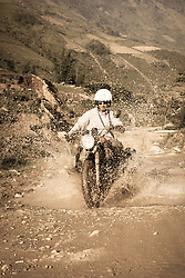 A Caucasian man drives his motorbike through mud on a mountain road in Sapa, Vietnam, Southeast Asia