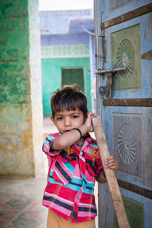 Boy standing in doorway of home in village of Chandelao
