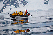 An adventure tourism team from the Scandinavian-built ice-breaker, Akademik Sergey Vavilov, watches humpback whales from an inflatable zodiac boat in Wilhelmina Bay, Antarctic Peninsula. The icebreaker was originally built for the Russian Academy of Science and although scientists still use it occasionally, it is now predominantly used for adventure touring in both the Arctic and the Antarctic. The ship is currently operated by a Russian crew, and staffed with employees of the adventure touring company Quark Expeditions, and carries around 100 passengers at a time.