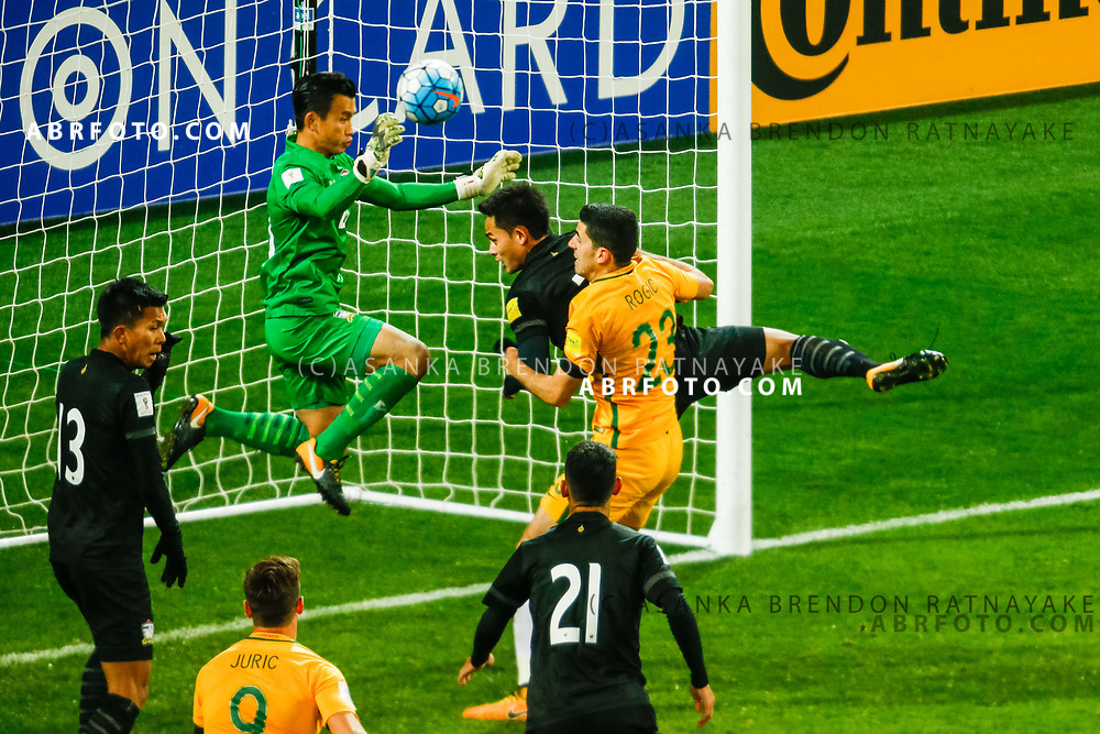 MELBOURNE, AUSTRALIA - SEPTEMBER 5 : Sinthaweechai Hathairattanakool of Thailand attempts to save the ball from Tomas Rogic of the Australia Socceroos  during the Stage 3 Group World Cup Football Qualifiers between Australia Vs Thailand at the Melbourne Rectangular Stadium, Melbourne, Australia 5 September 2017.