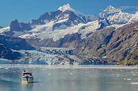 Sightseeing vessel in front of Johns Hopkins Glacier in Glacier Bay National Park and Preserve, Alaska.