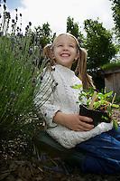 Girl (5-6) holding plants in garden portrait