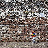 A boy walking before a stony wall in Khumjung which is plastered with round yak dung patties.