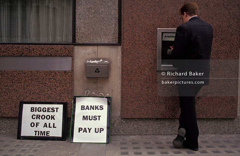 A businessman makes a cash withdrawal from an ATM at a time when the pension fund of Mirror Group Newspapers by its tycoon owner, Robert Maxwell was found to have been stolen from former employees, on 9th June 1992, in London, England.