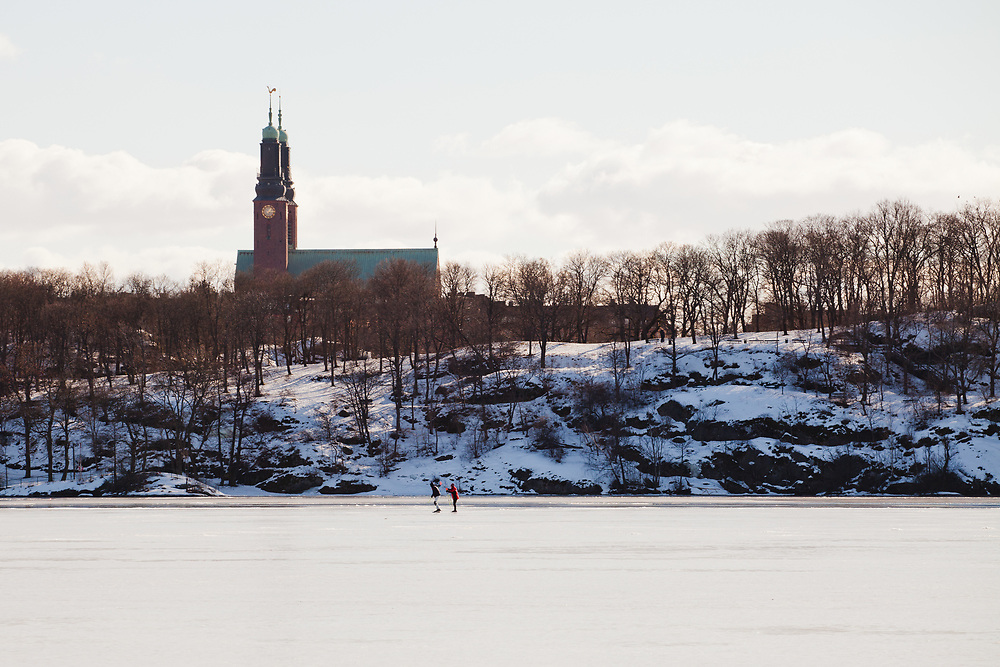 A couple skates through the frozen lake M&auml;laren, Riddarfj&auml;rden, in Stockholm.  The photo is taken from Kungsholmen with the island S&ouml;dermalm in the background.  <br />