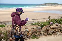 "© Licensed to London News Pictures. 11/05/2020. Newquay, UK. A woman wearing a mask walks past Fistral beach on the North coast of Cornwall, the day after British Prime Minister Boris Johnson announced a 'road map' to lift lockdown restrictions due to Covid-19, (Coronavirus). A rise in ""staycations"" - the concept of holidaying in your home country rather than travelling abroad - is expected, with many visitors planning to visit Cornwall. However, an ongoing campaign titled ""#ComeBackLater"" is trying to persuade tourists not to visit the county until it is safe to do so. Photo credit : Tom Nicholson/LNP"