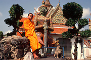 THAILAND, BANGKOK Wat Arun Temple; colorful mosaic inlaid guardian figure with seated monk
