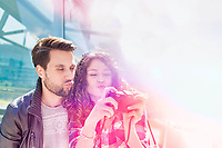 Portrait of young attractive woman taking selfie with her boyfriend in the middle of the city with lens flare in background