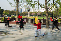 Shanghai, China - April 7, 2013: people exercising tai chi with fan in gucheng park in the city of Shanghai in China on april 7th, 2013