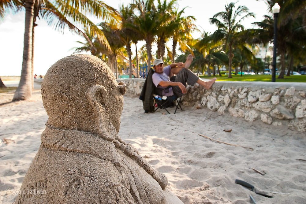 A sand sculptor shows off some of his latest work in South Beach, Miami, Florida.  The sand sculptures are done in order to make some money (as in donations) from people passing by.  The sculptures last only a few days then they get recycled.
