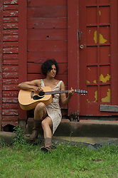 African American woman sitting strumming her guitar