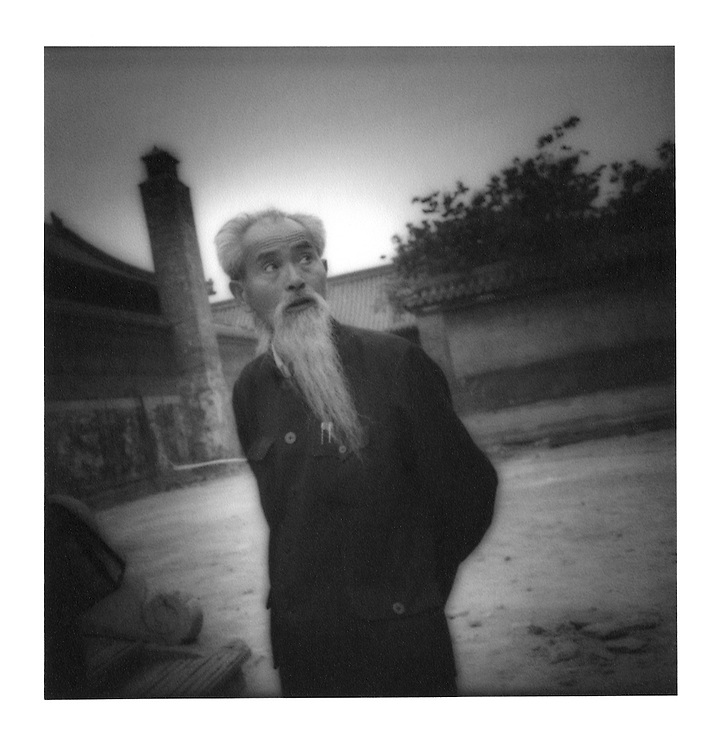 "Bearded elder surveys the courtyard of a ""hutong"" (alley).  Beijing, China.  1995"